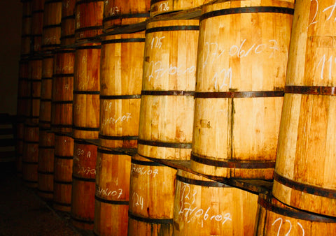 barrels aging stacked atop each other in a distillery