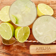 Two Classic Caipirinha cocktails surrounded by limes on a wooden table.