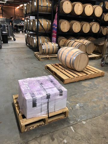Cases of whiskey on the ground in a warehouse in front of whiskey barrels