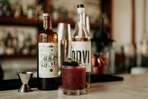 A bar with a bottle of ODVI Armagnac, Ancho Chili Reyes Liqueur, and a Sangres cocktail sitting on it.