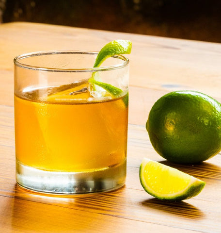 Light cocktail in a rocks glass with a lime peel garnish on a wooden table.