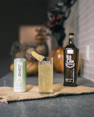 a highball cocktail tableau with two bottles of whiskey and Lunar, a craft hard seltzer paired with the drink, which is garnished with a slice of ginger