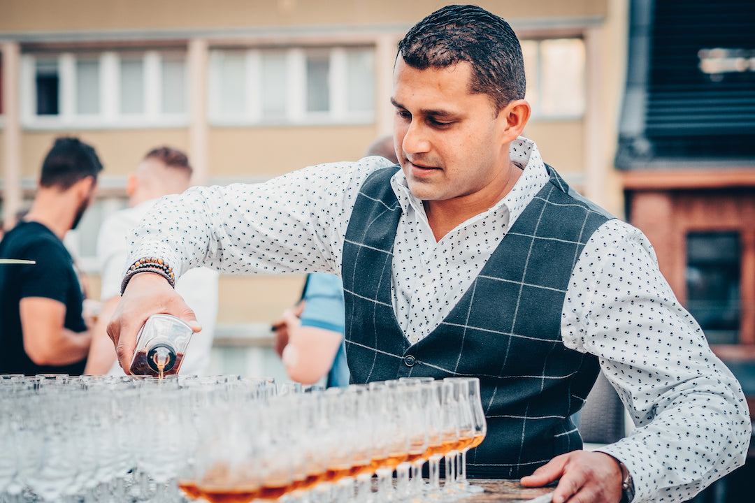 Karthik Sudhir, a man pouring rum into a glass at a festival.