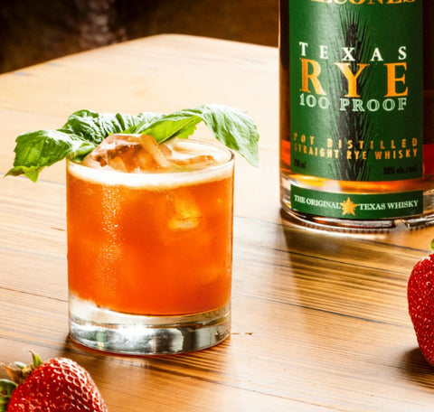 Bright strawberry cocktail with green garnish on a wooden table along side Strawberries and a bottle of Balcones Texas Rye