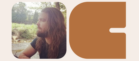 Whiskey taster, Josh Case, a man with long hair and blue shirt on sitting out side. A Curiada logo.