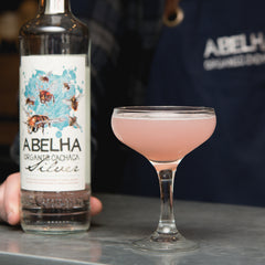 Bottle of Abelha Prata Cachaca on a stone table next to an elegant cocktail glass with a pink cocktail in it.