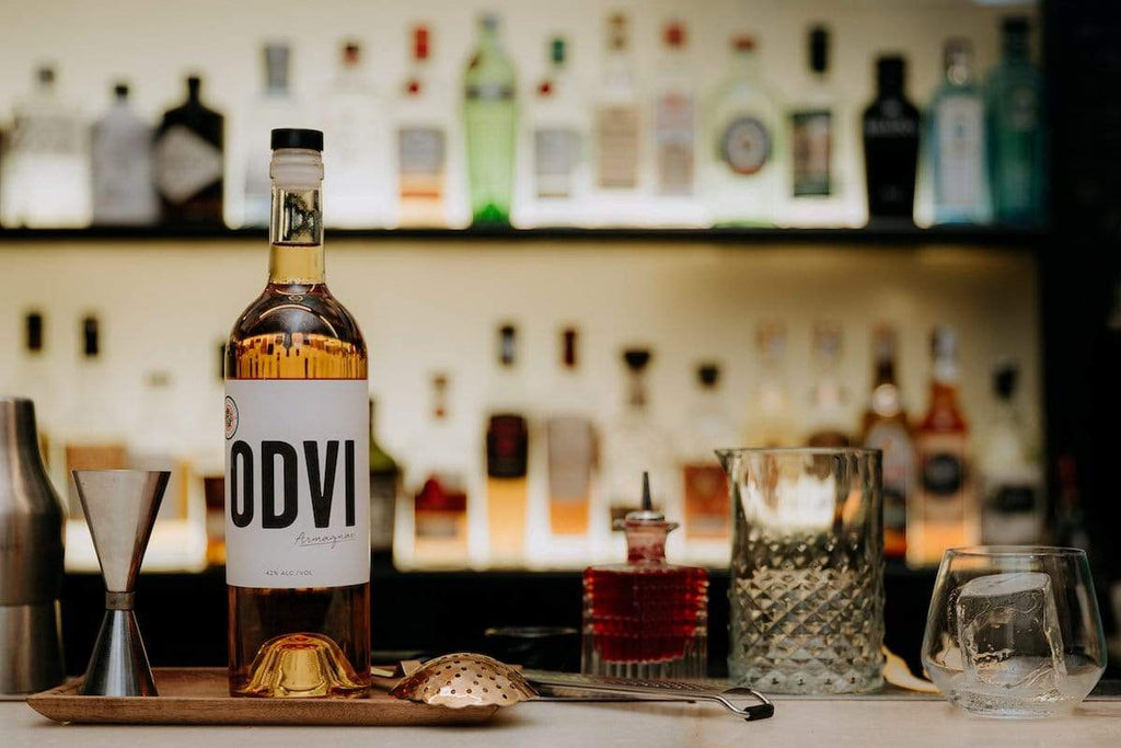 Bottle of ODVI Armagnac sitting on a bar, next to a jigger and other barware.