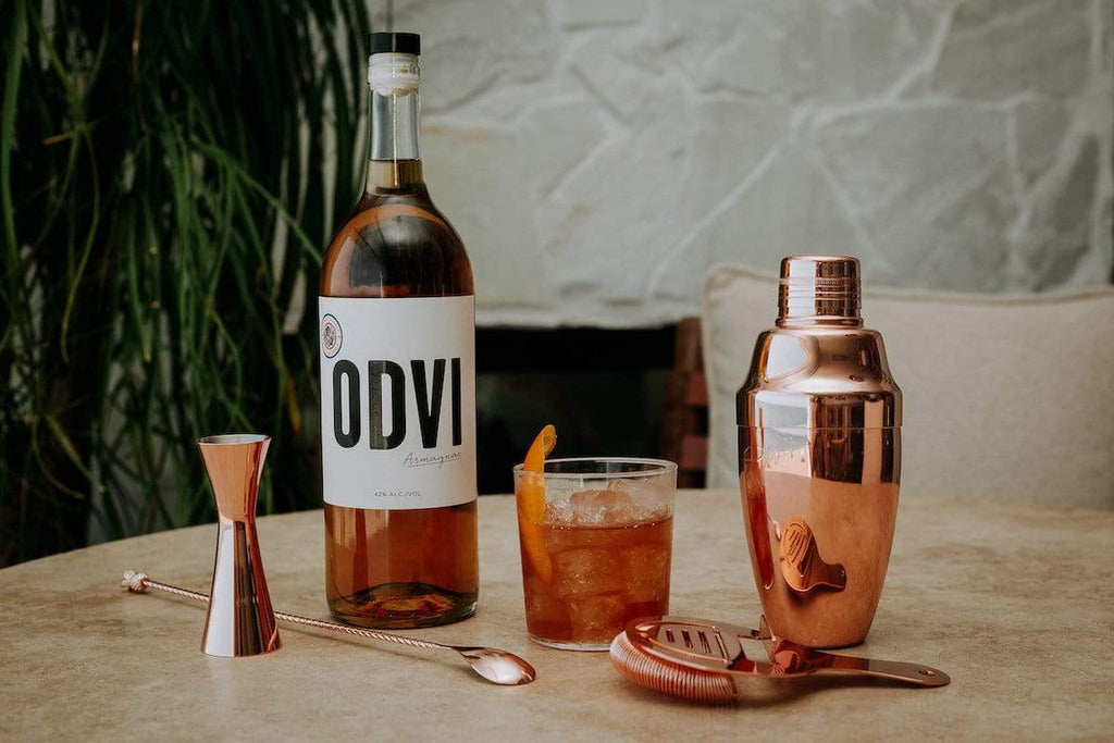 Bottle  of ODVI Armagnac on an outdoor patio table next to gold barware, shaker, jigger and a light cocktail.