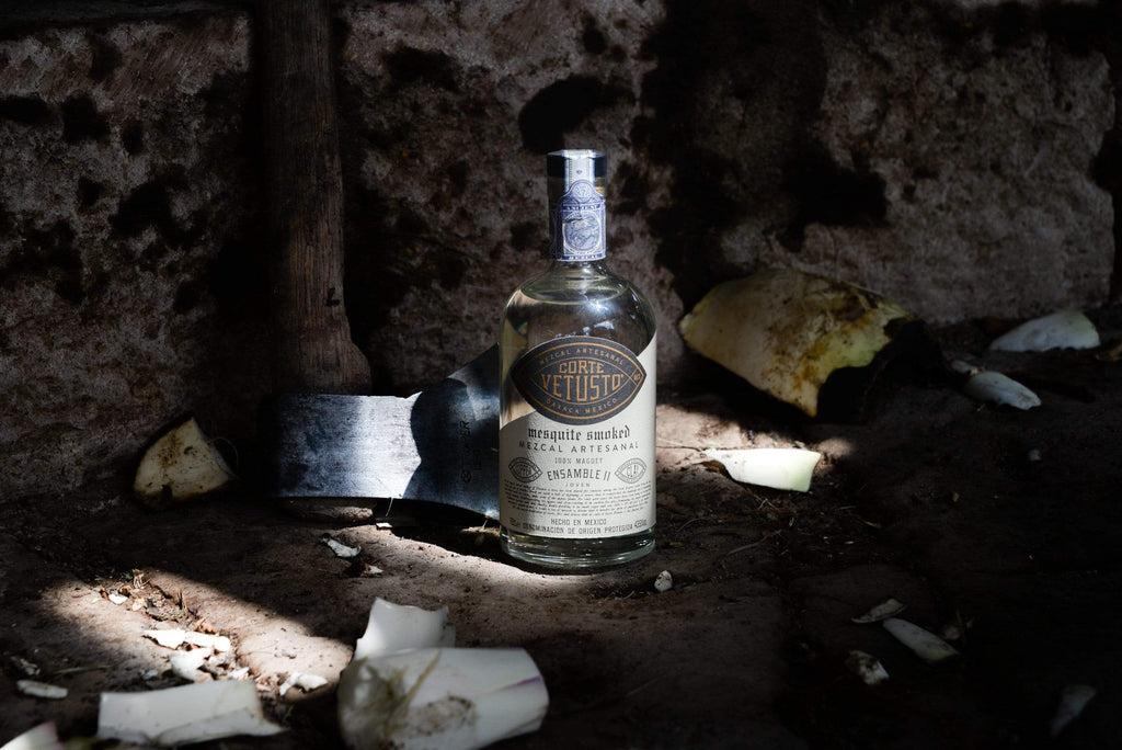 Bottle of Corte Vetusto Ensamble II Mezcal on the ground in a dark cave