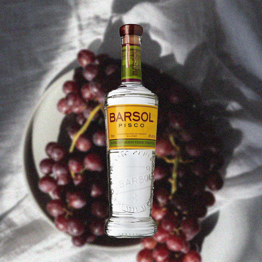 Bottle of Barsol Pisco Supremo on a background of a table with grapes.