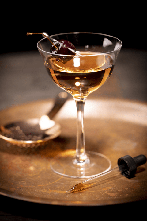 Glass of bourbon with decadent cherry, on a gold plate with silverware and a dropper.