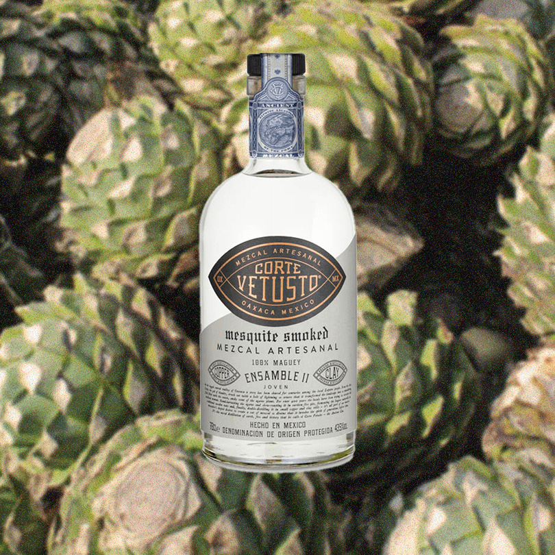 Bottle of Corte Vetusto Ensamble II Mezcal over a backdrop of Agave plants