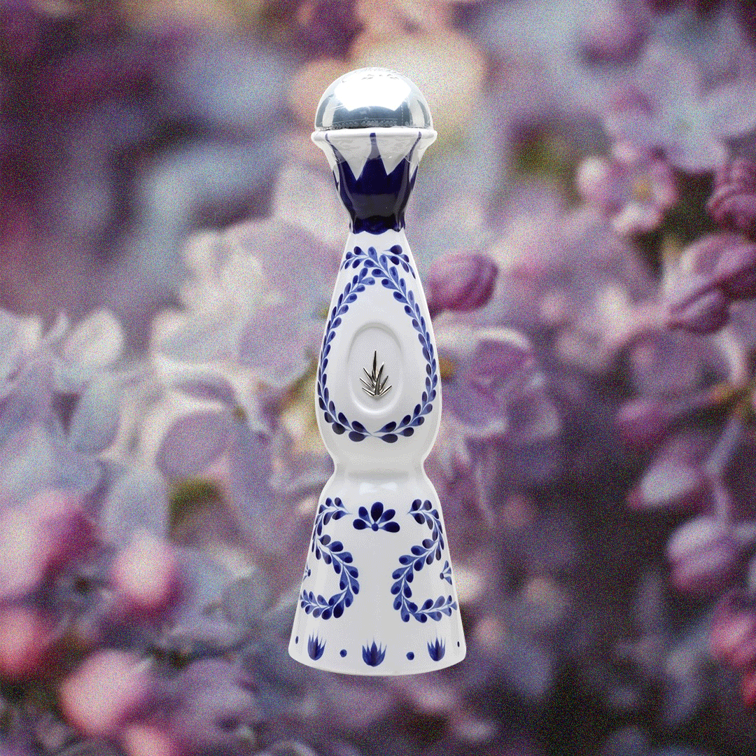 Clase Azul Reposado Tequila in a handmade bottle over a purple flower background.