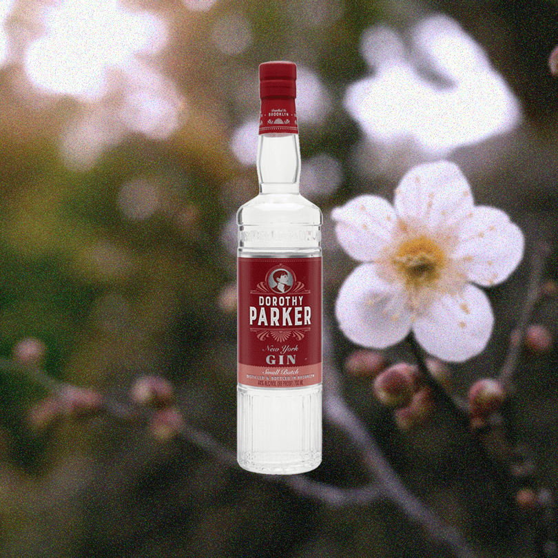Bottle of Dorothy Parker Gin on a background of a summer day with a bright flower.
