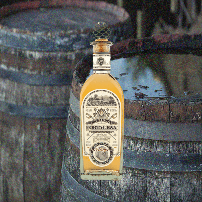Bottle of Fortaleza Tequila Añejo imposed over an image of two rustic barrels.