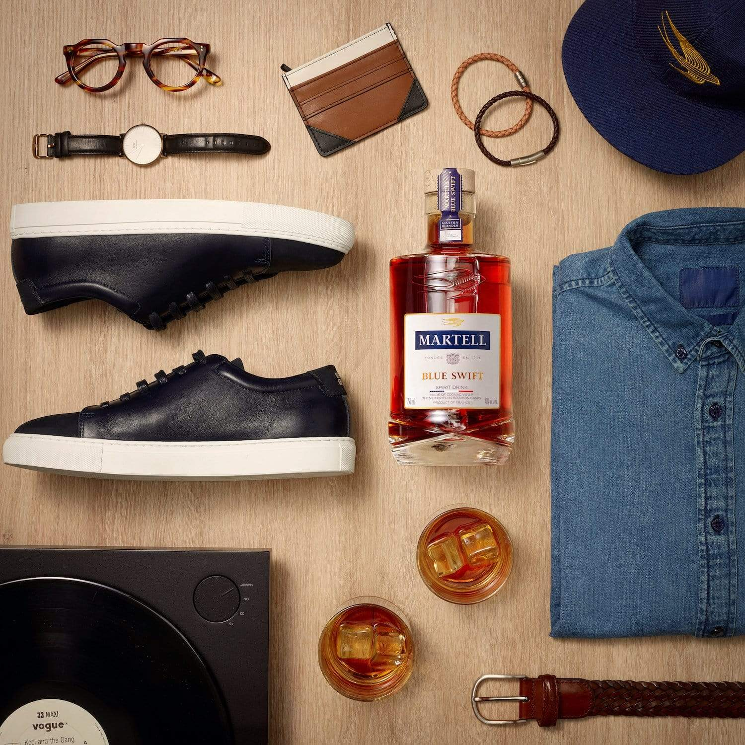 Blue Swift Martell Cognac on a table with shoes, shirt, watch and every day menswear items.