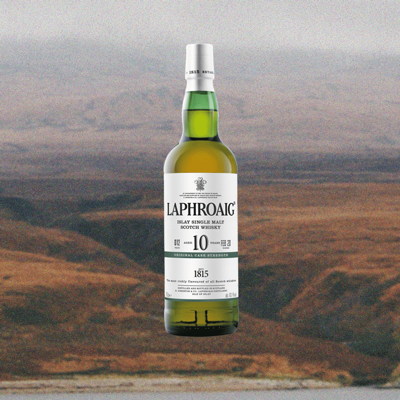 Bottle of Laphroaig 10 Year Cask Strength Single Malt Scotch over a faded picture of a sprawling valley