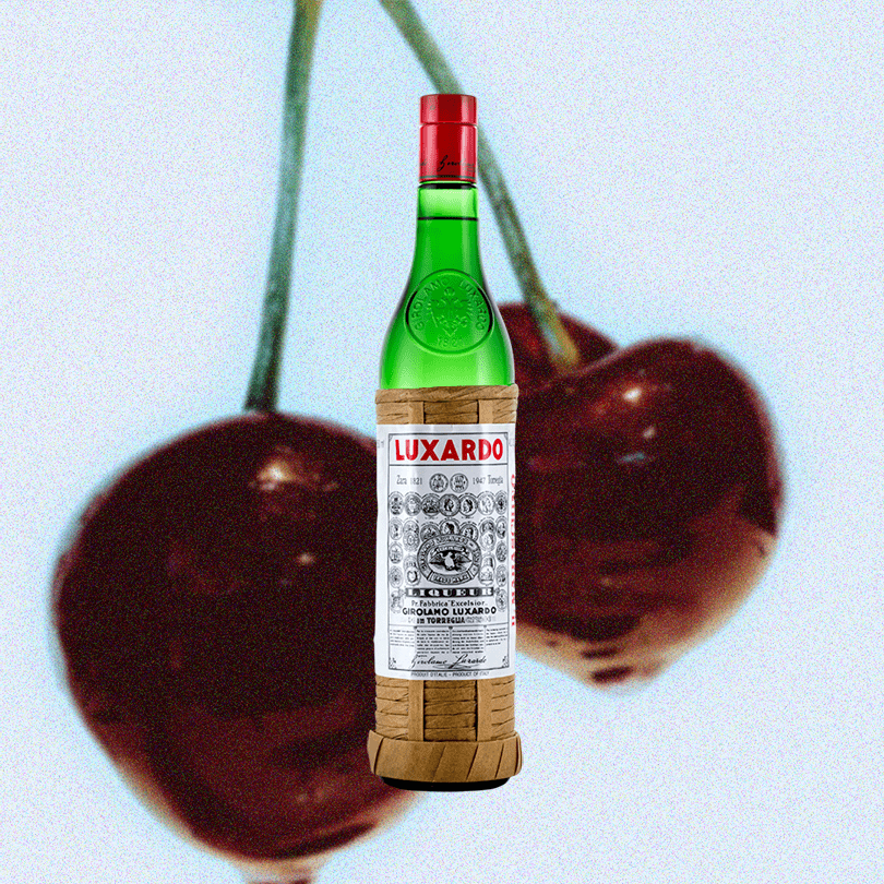 Bottle Luxardo Maraschino Liqueur over a background of decadent maraschino cherries.