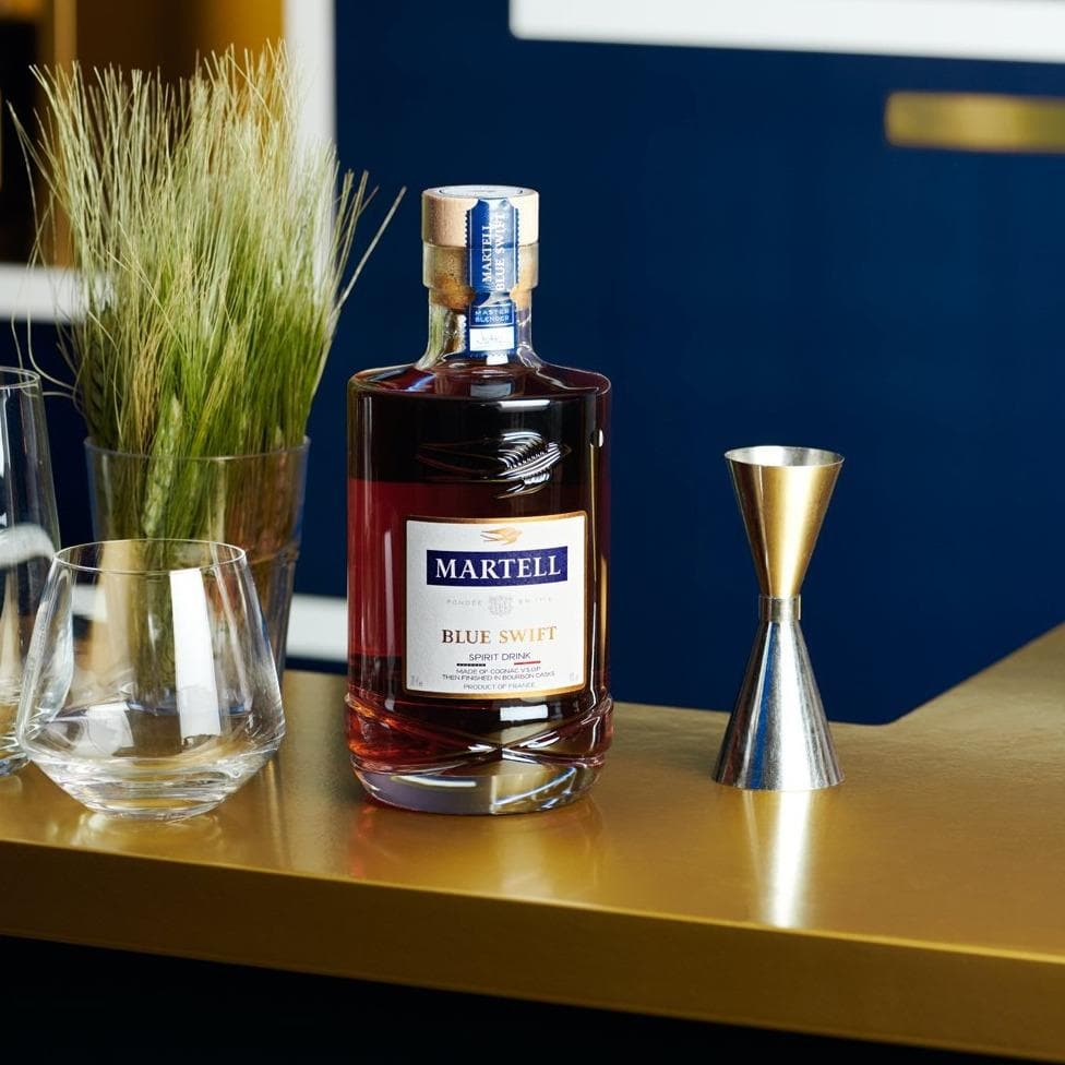 Martell Blue Swift Cognac on a beautiful table next to a plant a glass and a jigger.