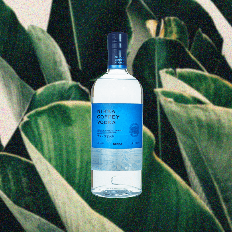 Bottle of Nikka Coffey Vodka over a backdrop of lush green plants.