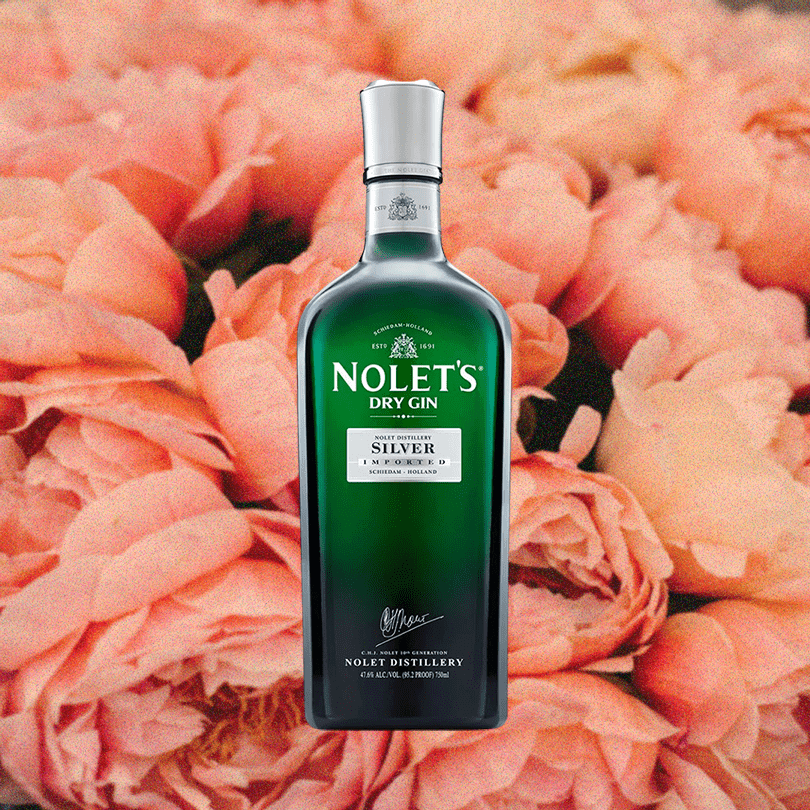 Bottle of NOLET'S Silver Gin over backdrop of light colored flowers.