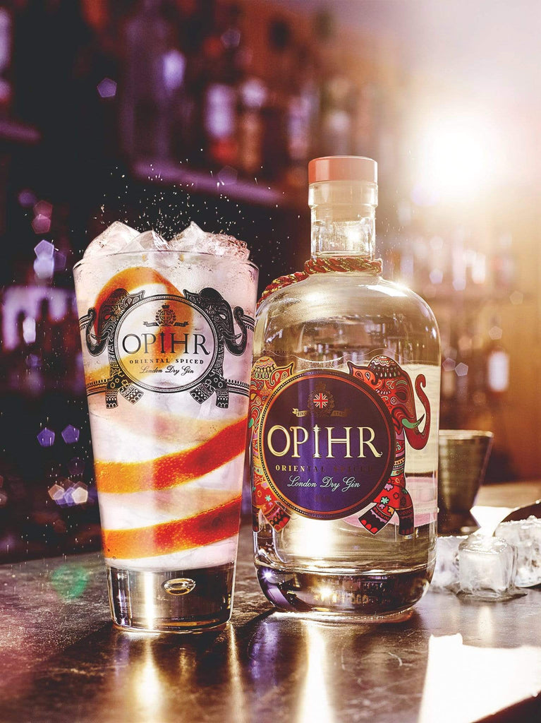 Bottle of Opihr Oriental Spiced London Dry Gin next to a cocktail glass on a bar with intense purple lighting.