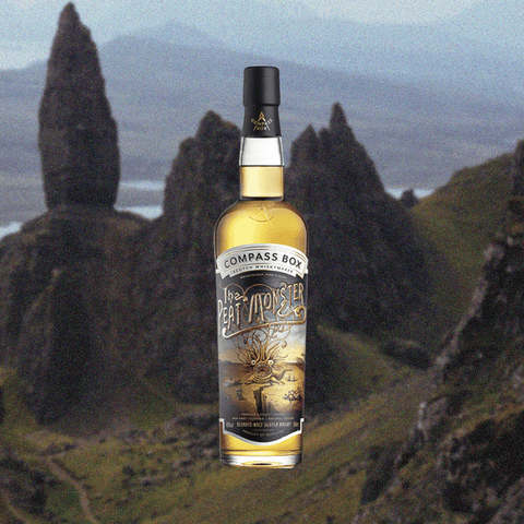 Bottle of Compass Box Peat Monster over backdrop of mountains and valleys.