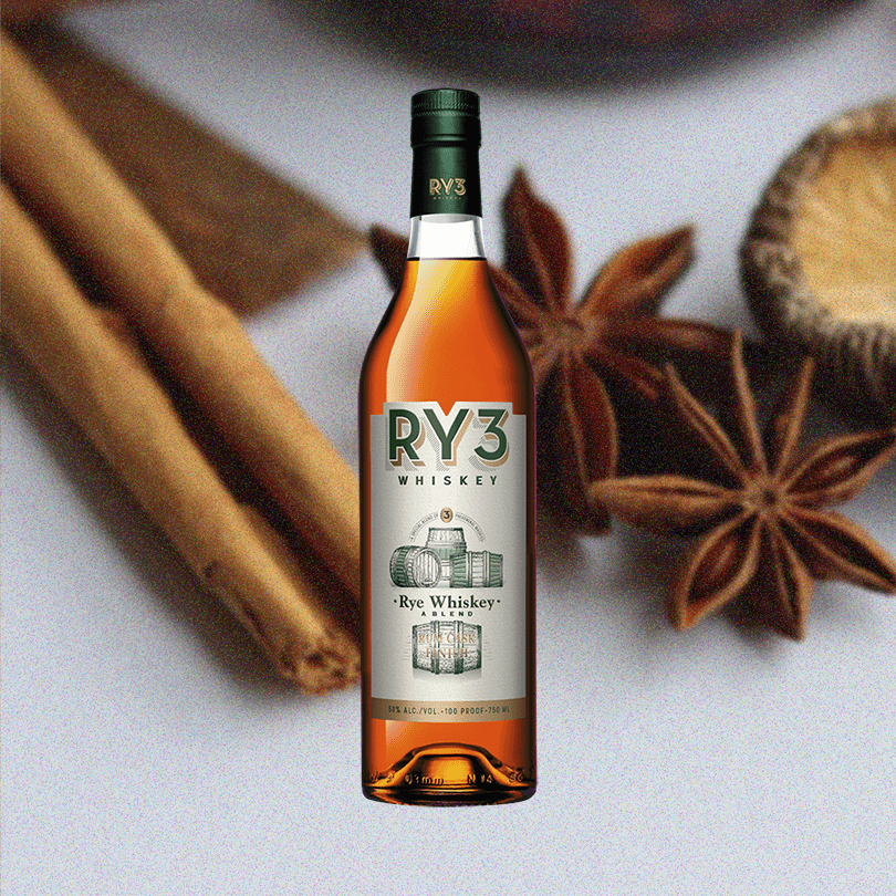 Bottle of RY3 Whiskey Rum Cask Finish over backdrop of cinnamon and similar spices on a table.