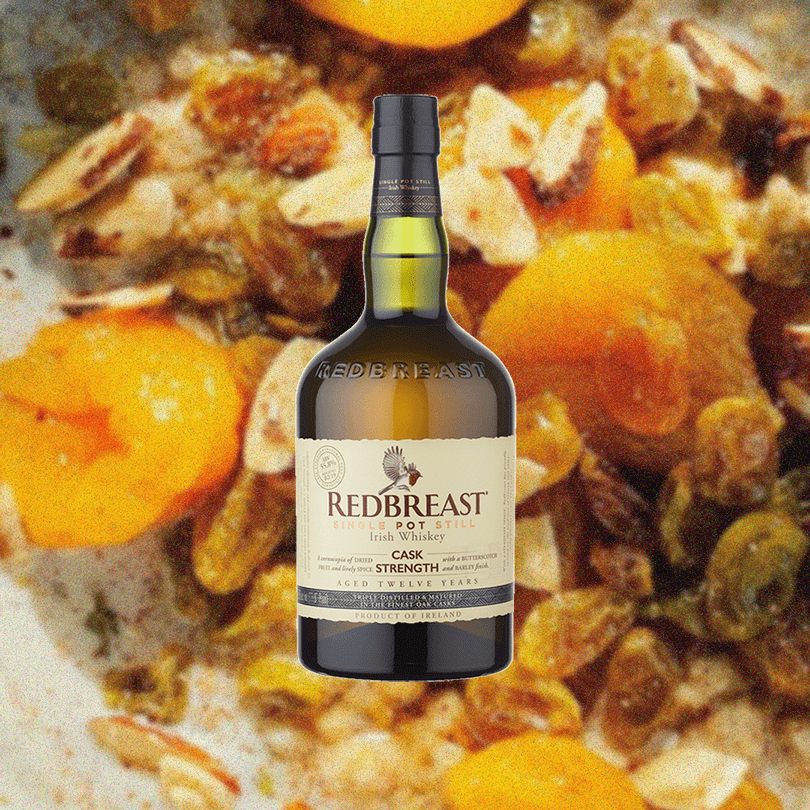 Bottle of Redbreast 12 Year Cask Strength Irish Whiskey over a backdrop of blurry dried fruit, perhaps apricots.