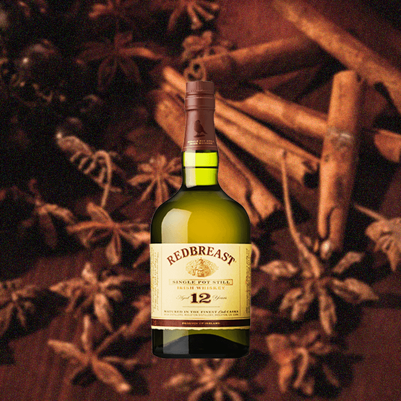 Bottle of Redbreast 12 Year Irish Whiskey over background of cinnamon and similar looking materials.
