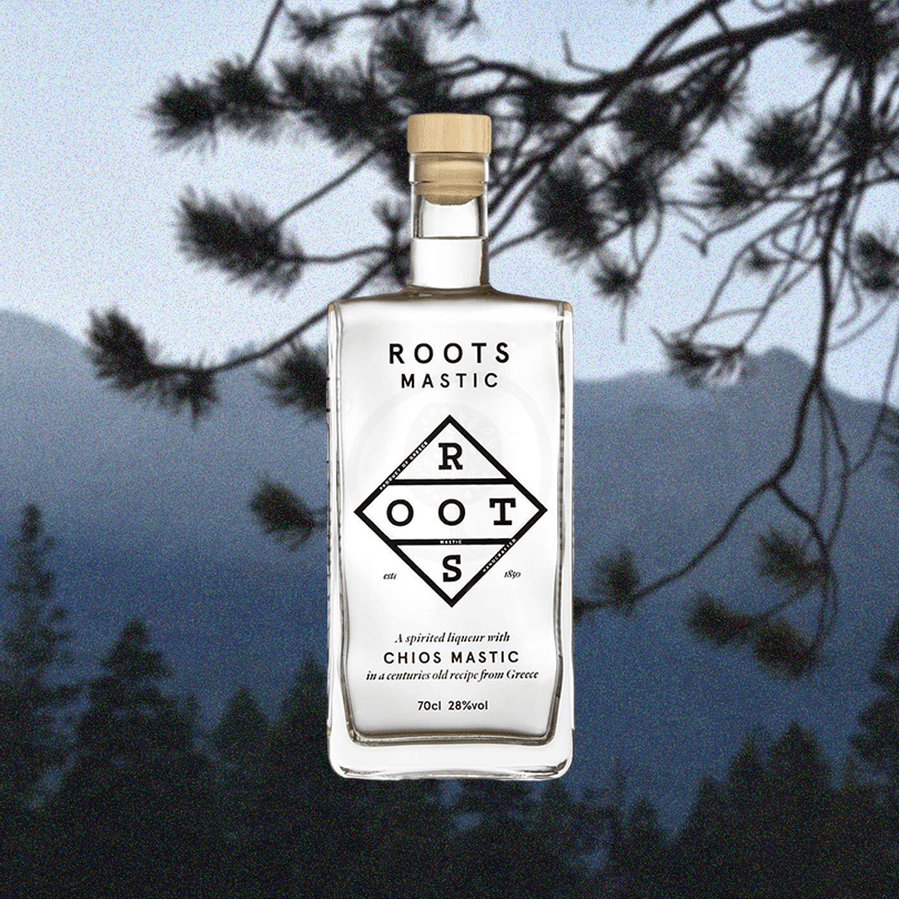 Bottle of Roots Chios Mastic Liqueur over a backdrop image of a pine tree and mountains.