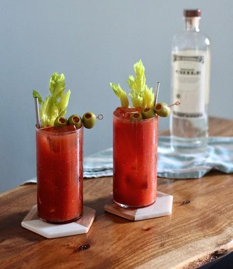 Two Bloody Marys on a table, made with St. George Green Chile Vodka