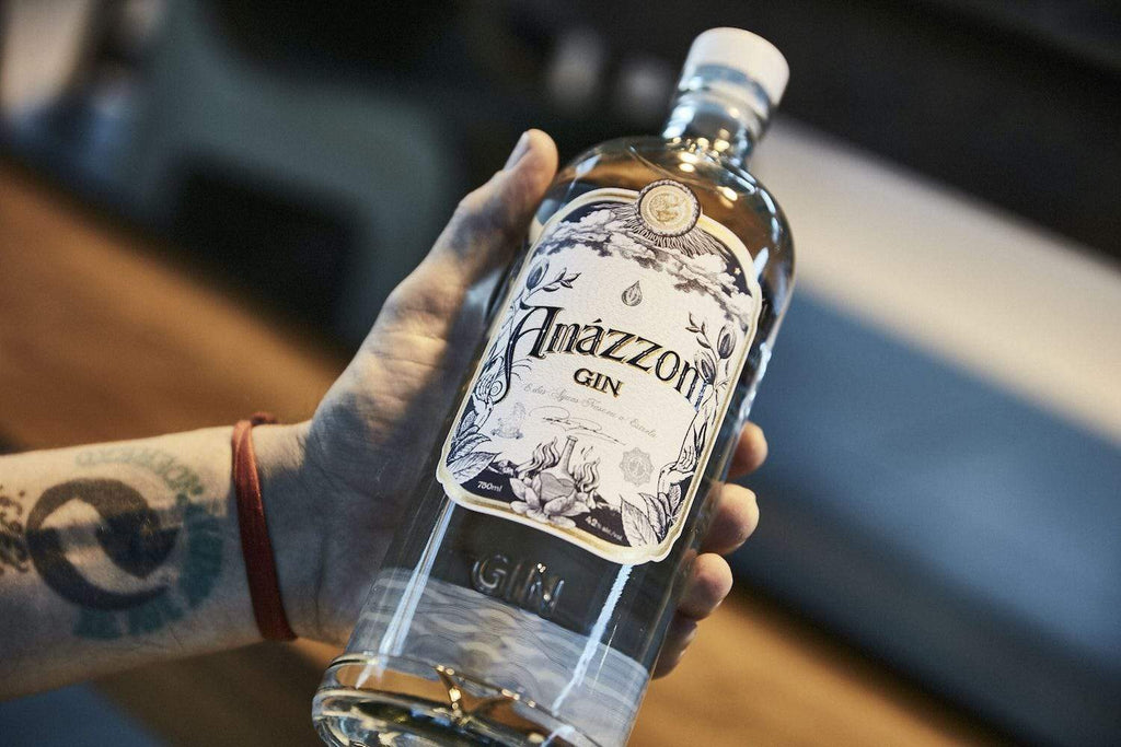 Amazzoni gin bottle in the hands of a man with a tattoo on his wrist.