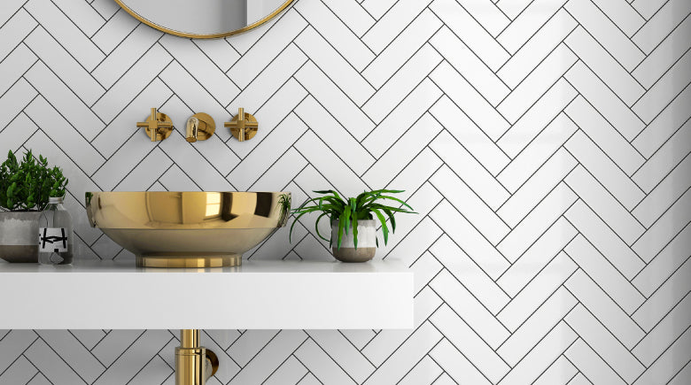 White subway tiles with black grout in bathroom with gold washbasin