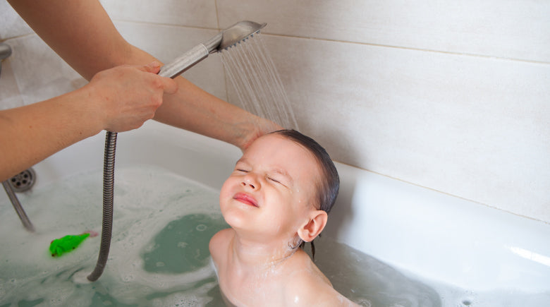 Mom washing childs hair in the bath