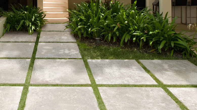 Outdoor porcelain paving tiles laid on grass