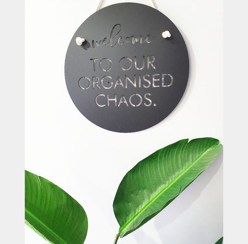 """Welcome to our organised chaos"" sign"
