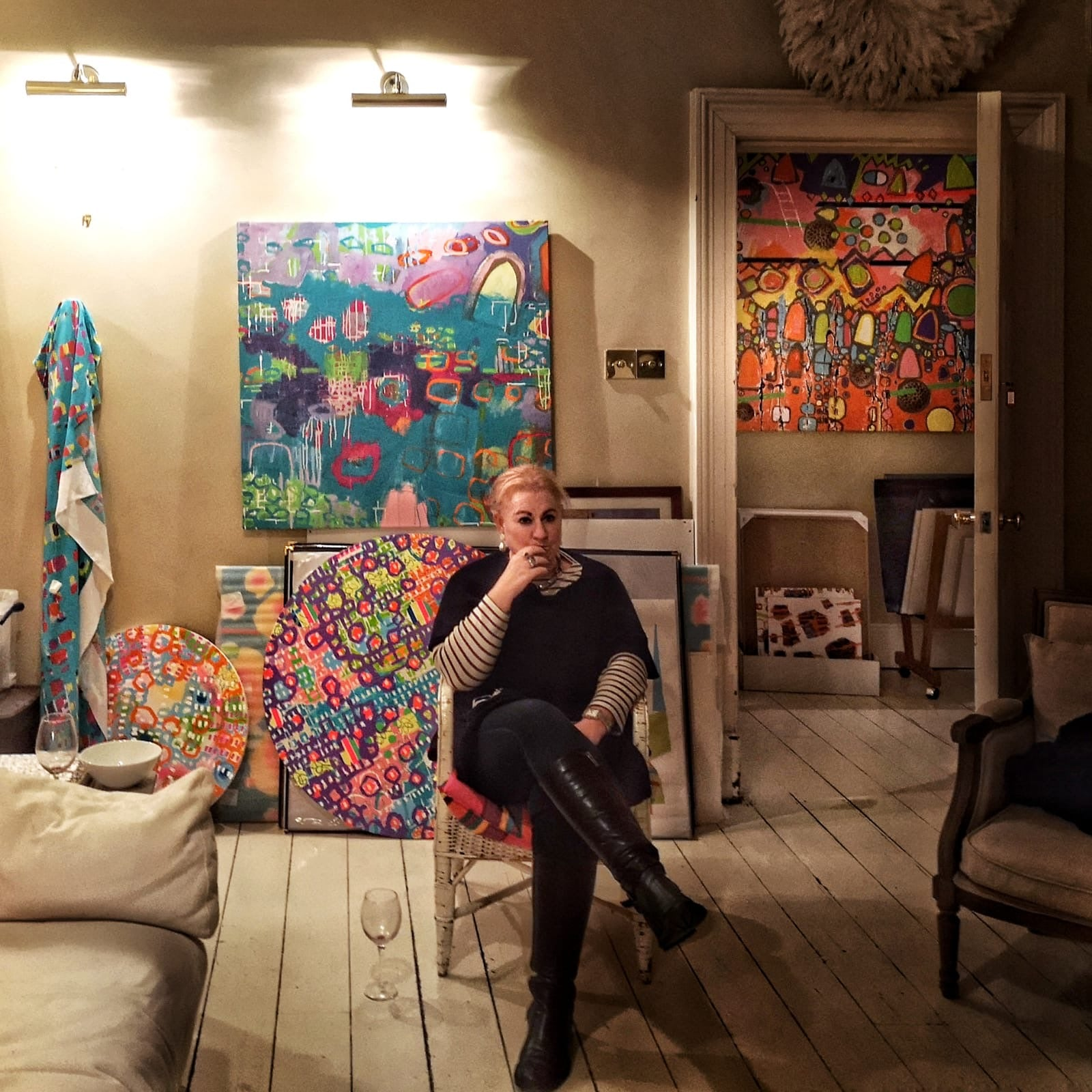 Julia Krone Oliver sitting amongst her abstract art paintings