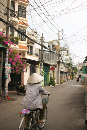 lady biking away in an alleyway in vietnam