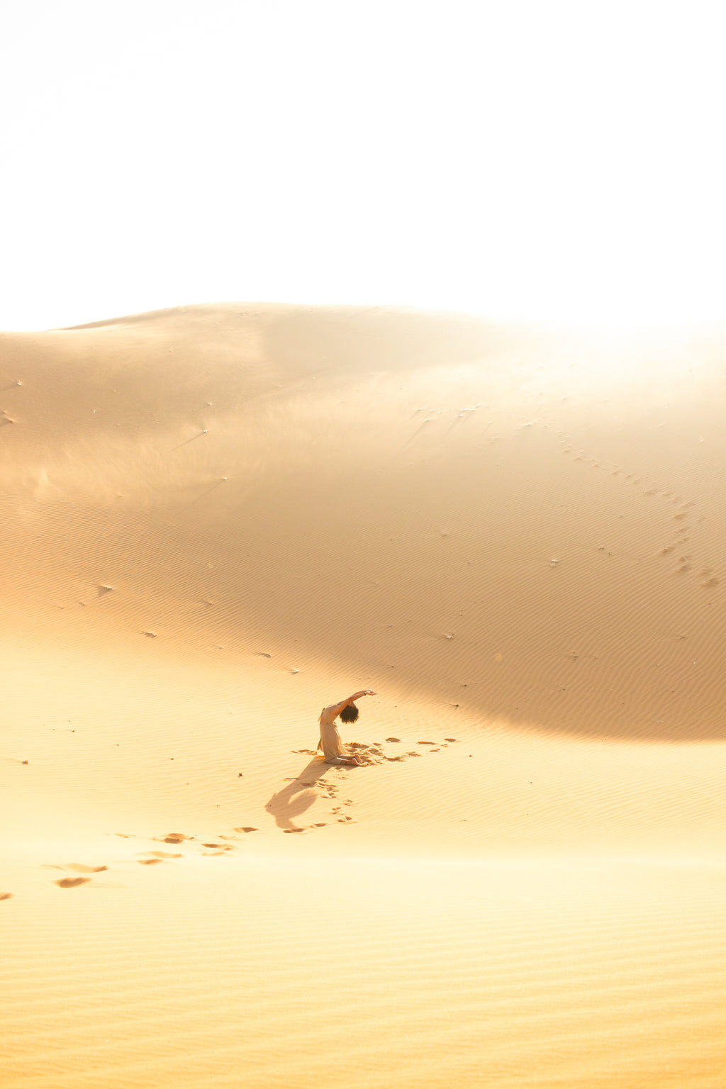 girl in the middle of sand dunes during golden hour sunset