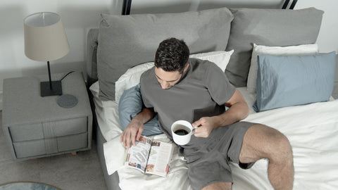 Male model lying on bed having coffee wearing restlab's Equilibrium Sleep Set