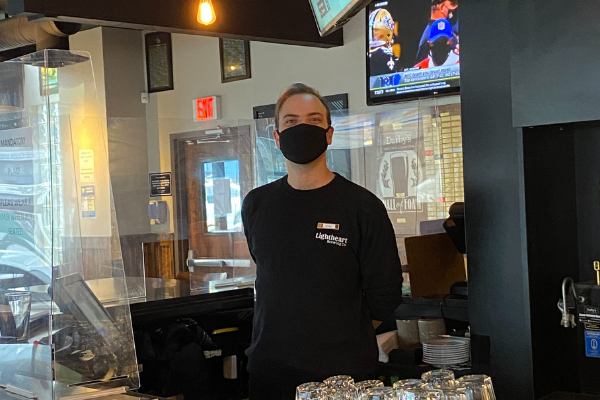 masked darby's worker standing at the bar cash register
