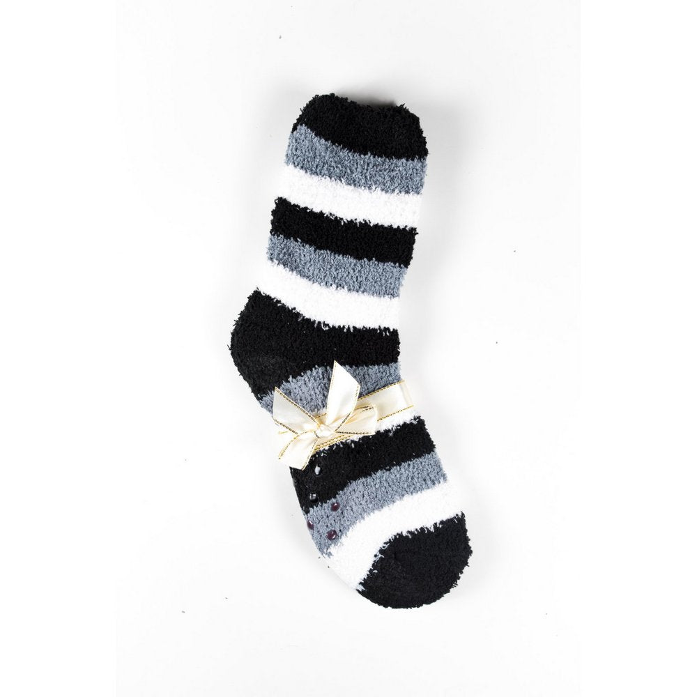 Cosy bed socks for women with non-slip bottoms in black grey stripes, flat lay showing gift packaging