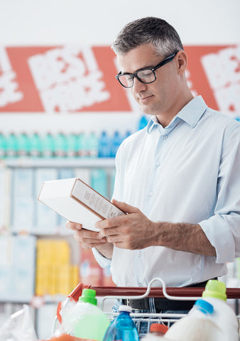 man reading labels of food in the grocery store
