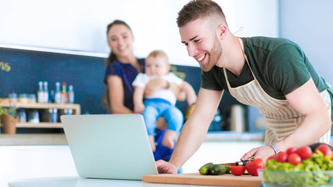 man in kitchen with mom and child cooking with veggies