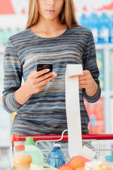 Woman looking at food bill in grocery store