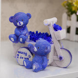 Tirelire Ours bleu sur un tricycle  de face