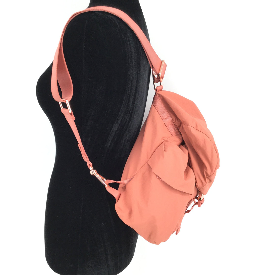 Medium Sized Nylon Coral Lulu Lemon Backpack  - <P>MEDIUM SIZED NYLON CORAL LULU LEMON BACKPACK WITH ROSE GOLD DETAILING. TWO POCKETS ON EACH SIDE WITH SNAP CLOSURE, ZIP POCKET ALSO ON THE TOP OF THE BACKPACK. DRAWSTRING CLOSURE AND TWO INTERIOR POCKETS. REMOVABLE STRAP THAT CAN ALSO BE ADJUSTED. BACKPACK IS IN GREAT CONDITION.</P>