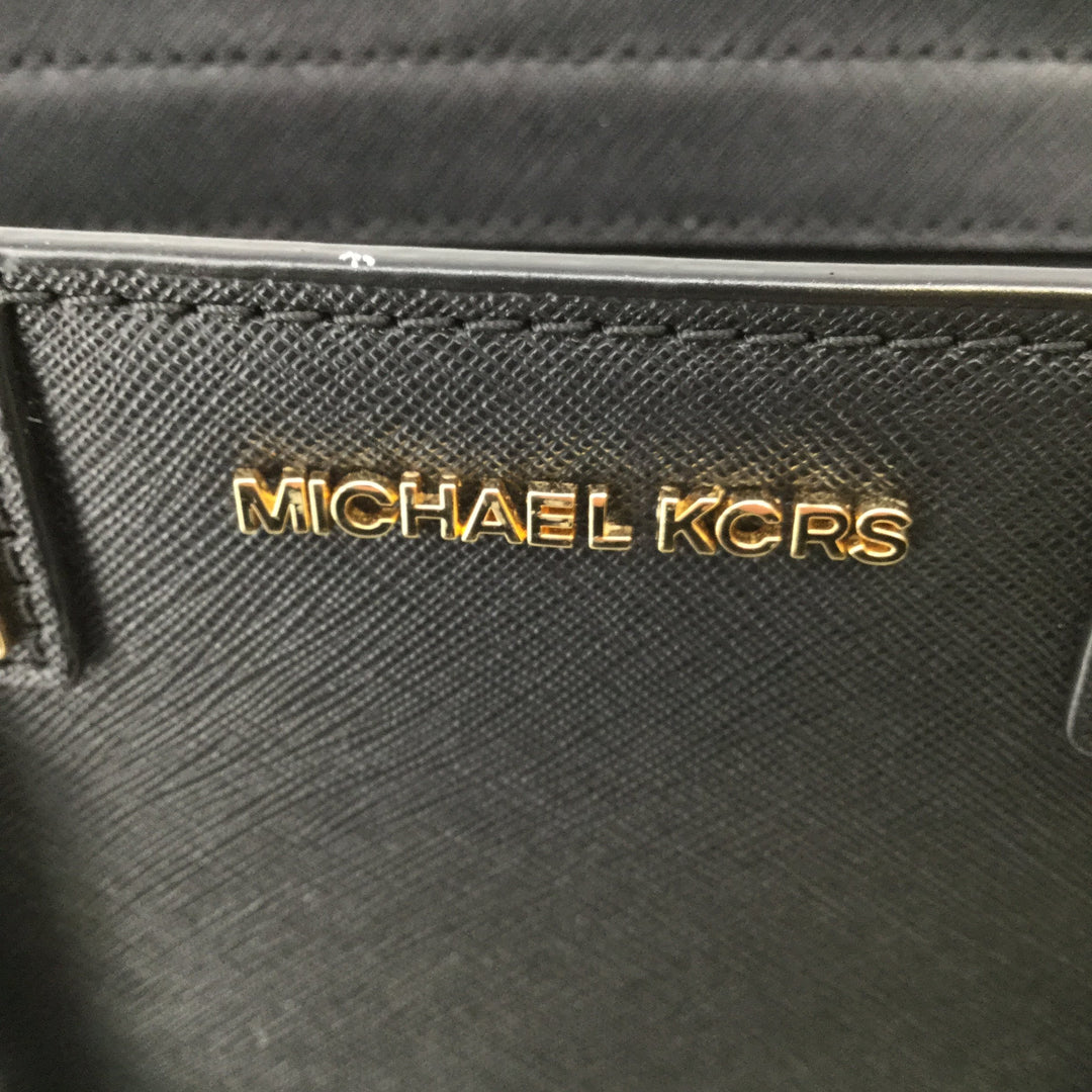 Leather Black Michael Kors Handbag - <P>LARGE LEATHER BLACK MICHAEL KORS HANDBAG WITH REMOVABLE STRAP. GOLD DETAILING AND REMOVABLE STRAP IS ALSO ADJUSTABLE. BLACK INTERIOR WITH CLASSIC MICHAEL KORS PATTERN AND ONE ZIPPERED POCKET AS WELL AS SEVEN OTHER POCKETS. GENTLY USED CONDITION.</P>