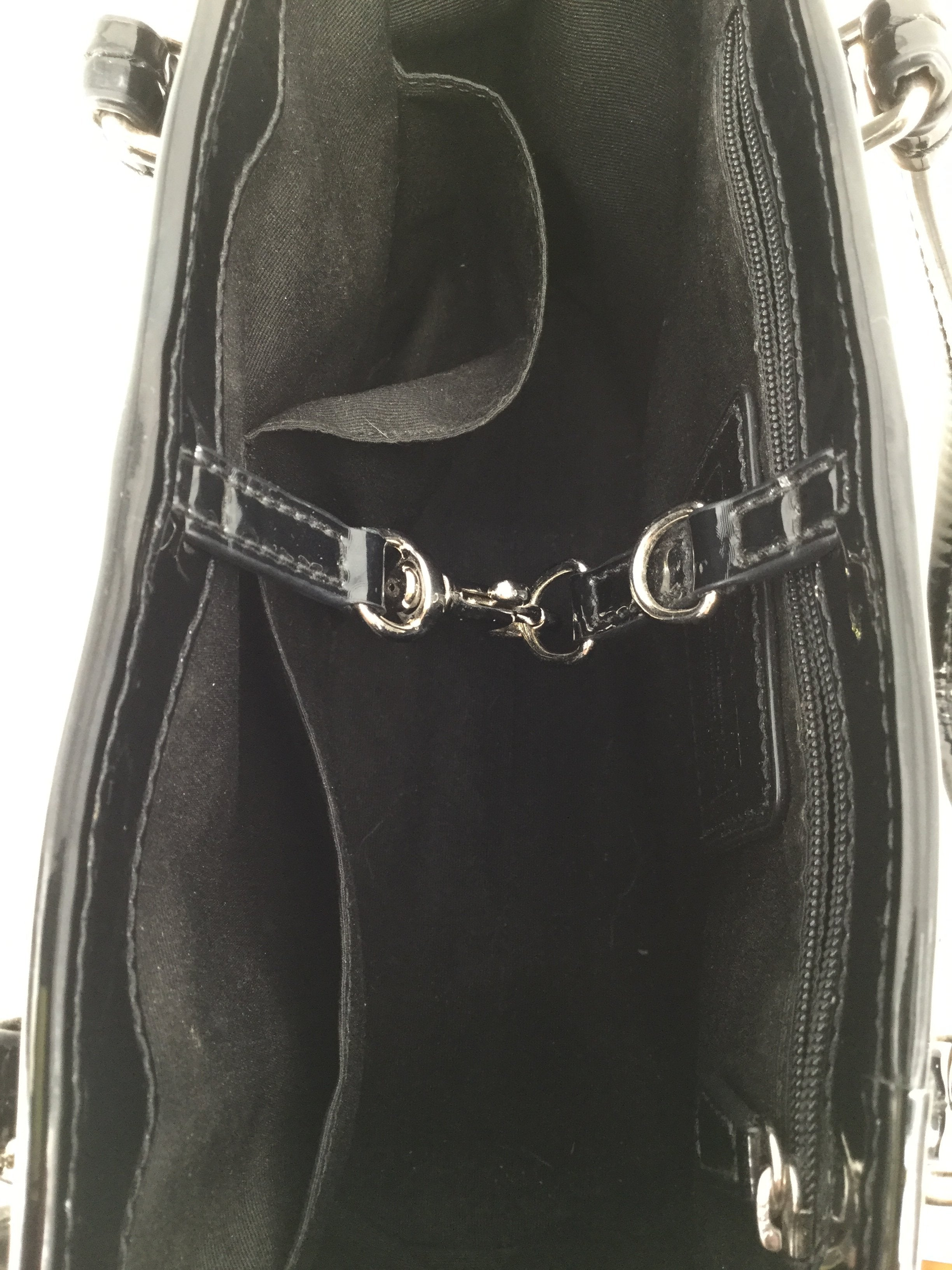 Small Black Patent Leather Coach Handbag - <P>SMALL BLACK PATENT LEATHER COACH HANDBAG. SILVER DETAILING AND CLASSIC COACH LOGO ALL OVER THE BAG. BLACK INTERIOR WITH ONE ZIPPED POCKET AND TWO SMALLER POCKETS. OPEN DESIGN WITH HOOK CLOSURE. GENTLY USED.</P>